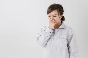鼻をつまむ作業着を着た女性