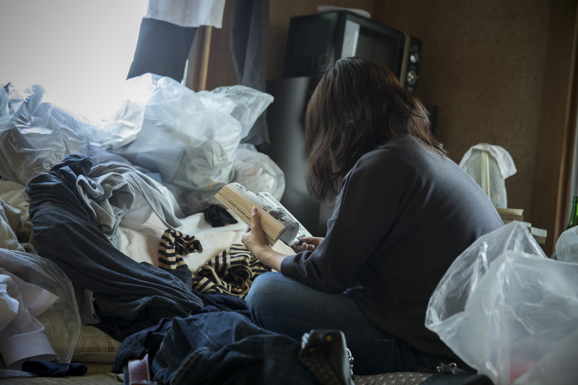 ゴミ屋敷の中で本を読む女性