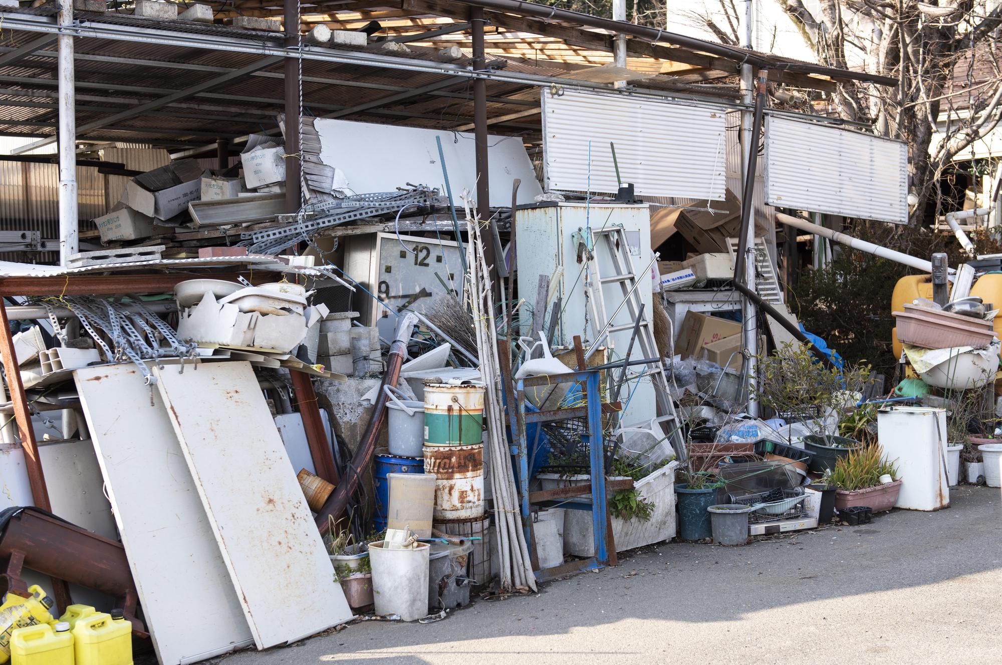 大量のゴミが外に積まれたゴミ屋敷