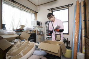 ゴミ屋敷の片付けをする女性